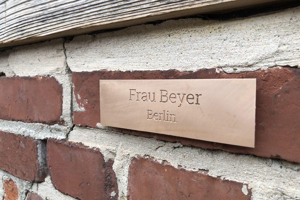 gefrästets Schild aus Bronze an Steinmauer