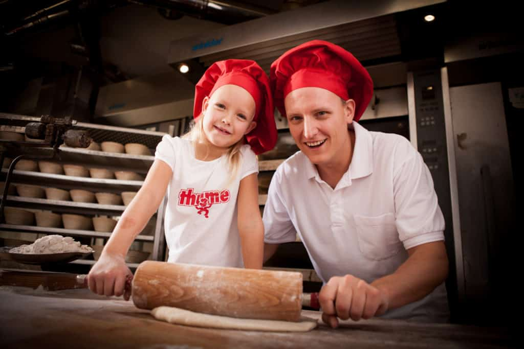 Produktfotografie Fotografie Bäckerei Thume, Mädchen hilft Bäcker beim Teig ausrollen.