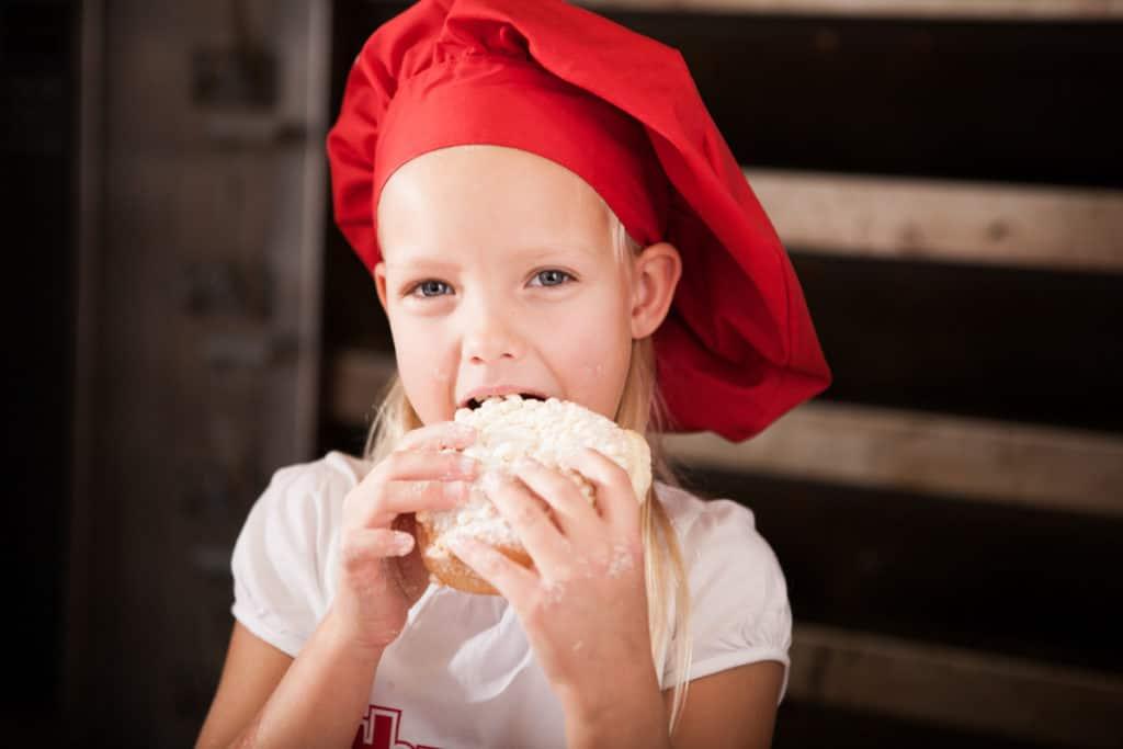 Produktfotografie Fotografie Bäckerei Thume, Mädchen mit Bäckermütze beißt in Streuselschnecke.