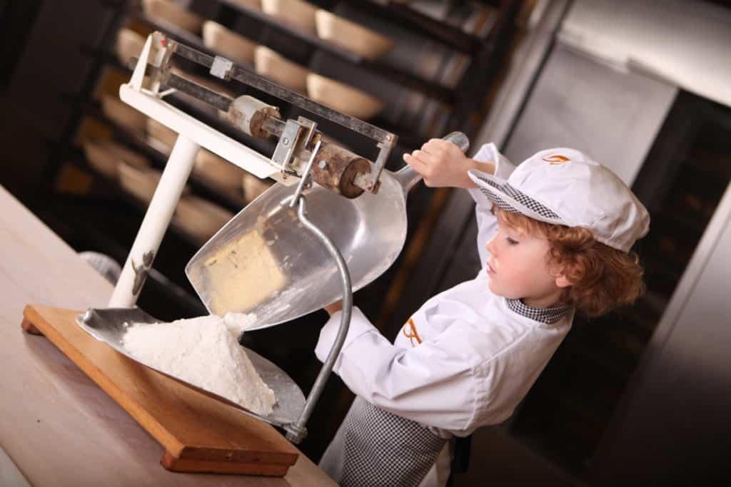 Fotografie Bäckerei Exner, Bäckerkind wiegt Mehl