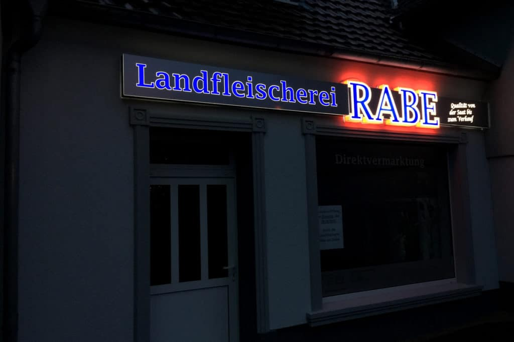 Werbebande mit Innenausfräsung von Alu-DiBond und gefräseten Buchstaben - Nachtansicht
